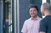 Two Polynesian male business colleagues share a joke outside the office in New Zealand