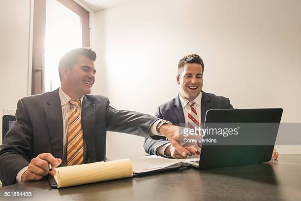 Two male business lawyers chatting in office