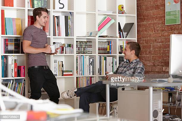 Two male colleagues chatting in office