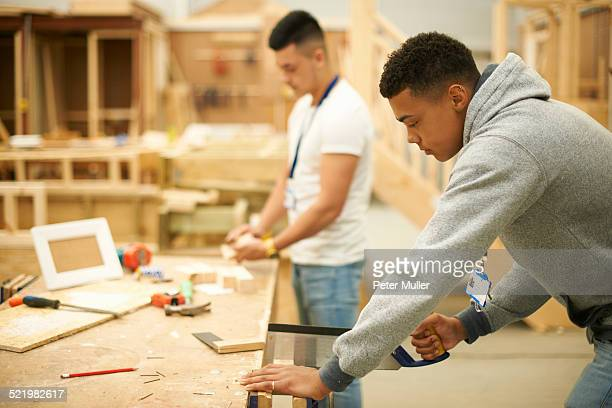 Two male college students in woodworking workshop