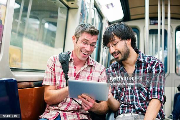 Zwei männlichen Pendler in U-Bahn Lachen an einem tablet arbeitet