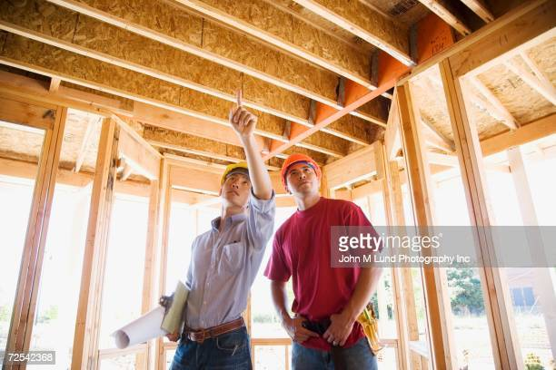 Two male construction workers inside construction site