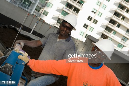 Two male construction workers working at a construction site : Stock Photo