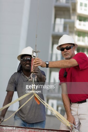 Two male construction workers working at a construction site : Foto de stock