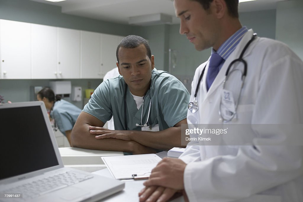 Two male doctors looking at medical chart : Stock Photo