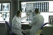 'Two male doctors looking at X-Rays and MRI scans, rear view'