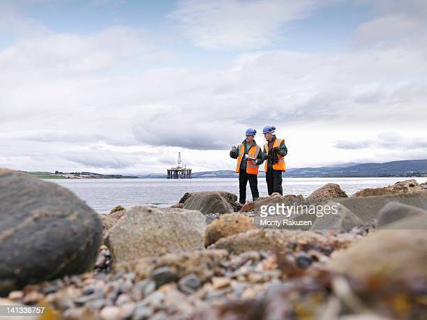 Two male environmentalists checking samples on seashore