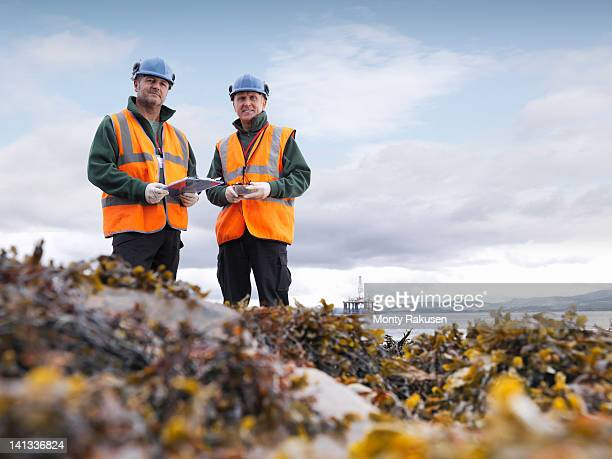 Two male environmentalists checking seaweed samples on seashore