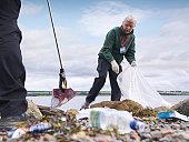 Two male environmentalists removing litter from seashore