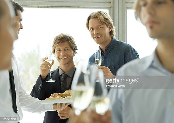 Two male executives raising glasses of champagne during office party