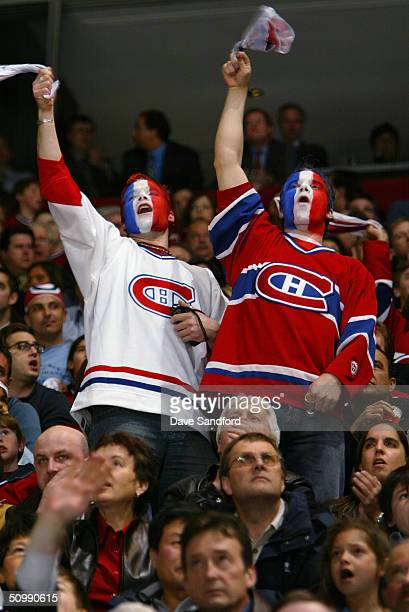 Two male fans of the Montreal Canadiens cheer for their team with their faces painted in team colors during game three of the eastern conference...
