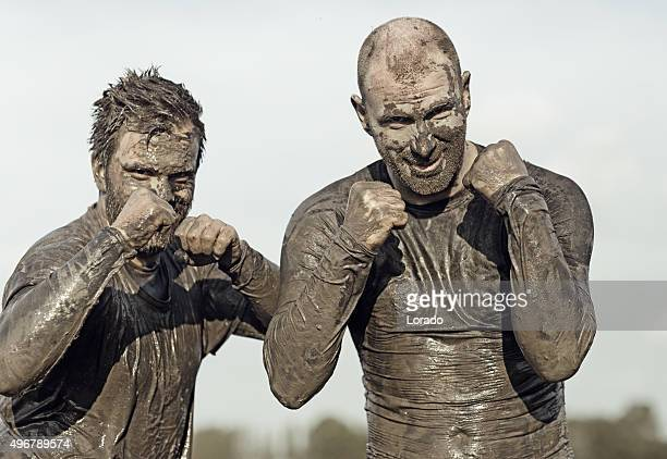 two male fighters covered in mud