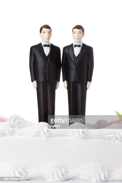 Two male figurines dressed in tuxedos atop a white cake