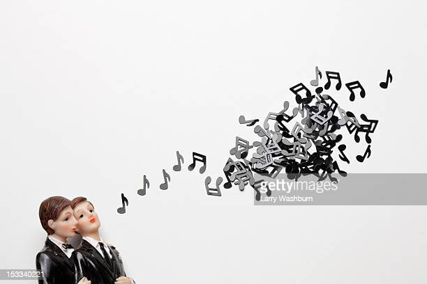Two male figurines next to a group of musical notes