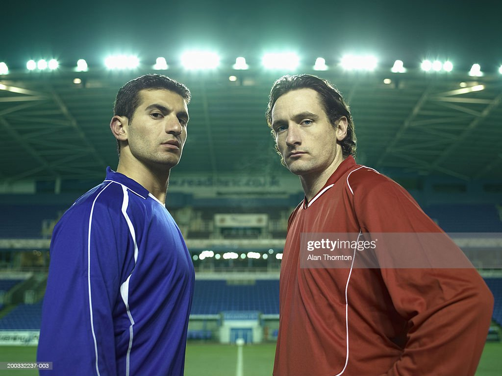 Two male football players on pitch, portrait, night : Stock Photo