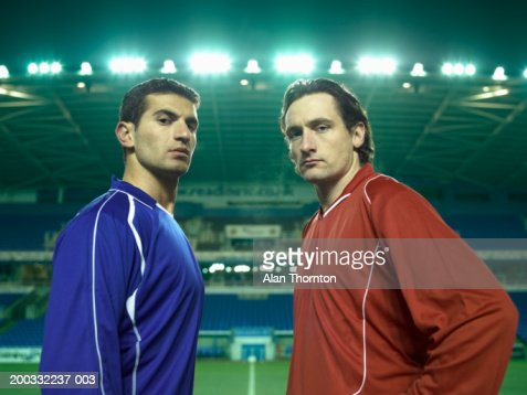 Two male football players on pitch, portrait, night : ストックフォト