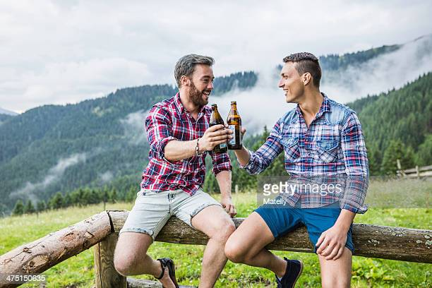 Two male friends drinking beer on fence, Tyrol Austria