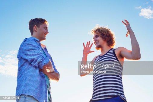 Two male friends enjoying conversation in sunlight