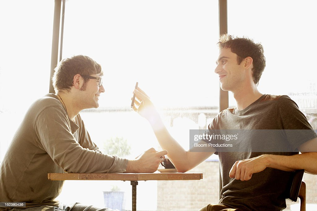 two male friends in a cafe using technology : Stock Photo
