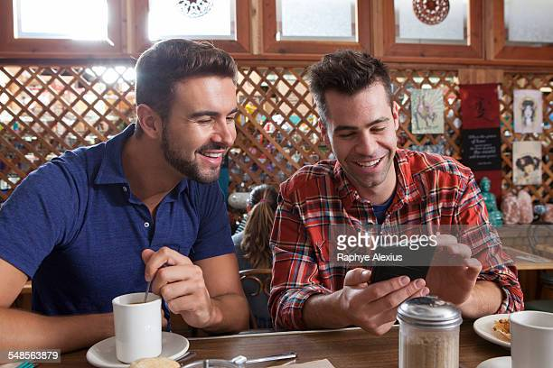 Two male friends looking at smartphone at restaurant bar
