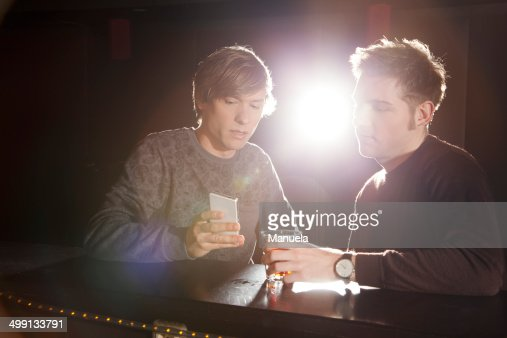 Two male friends looking at smartphone in nightclub : Stock Photo