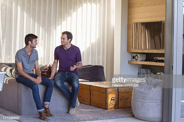 Two male friends looking each other and smiling