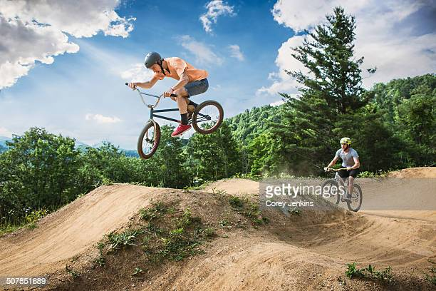 Two male friends riding BMX and mountain bikes on rural pump track