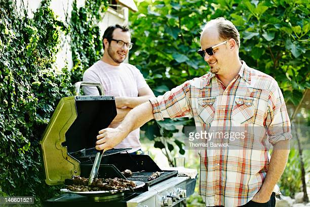 Two male friends standing around while barbecuing