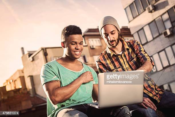 Two male friends working on laptop