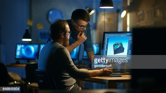 Two Male Game Developers Discuss Game Level Drawing, One Uses Graphic Tablet. They Work Late at Night in a Loft Office. : Stock Photo