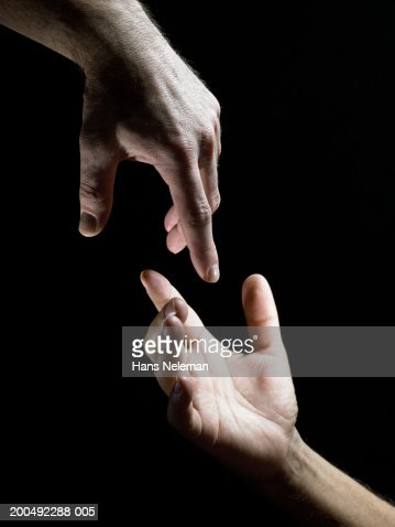 Two male hands reaching towards each other, close-up, side view : Stock Photo