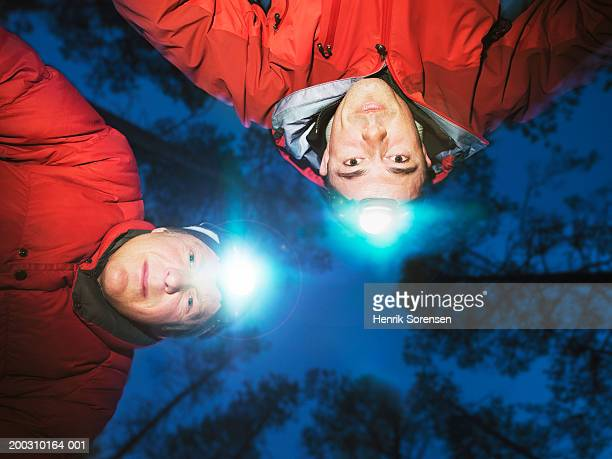 Two male hikers wearing head torches, portrait, low angle view