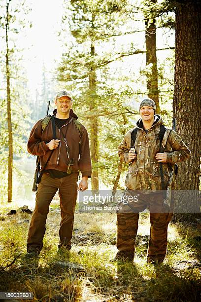 Two male hunters standing in woods with rifles