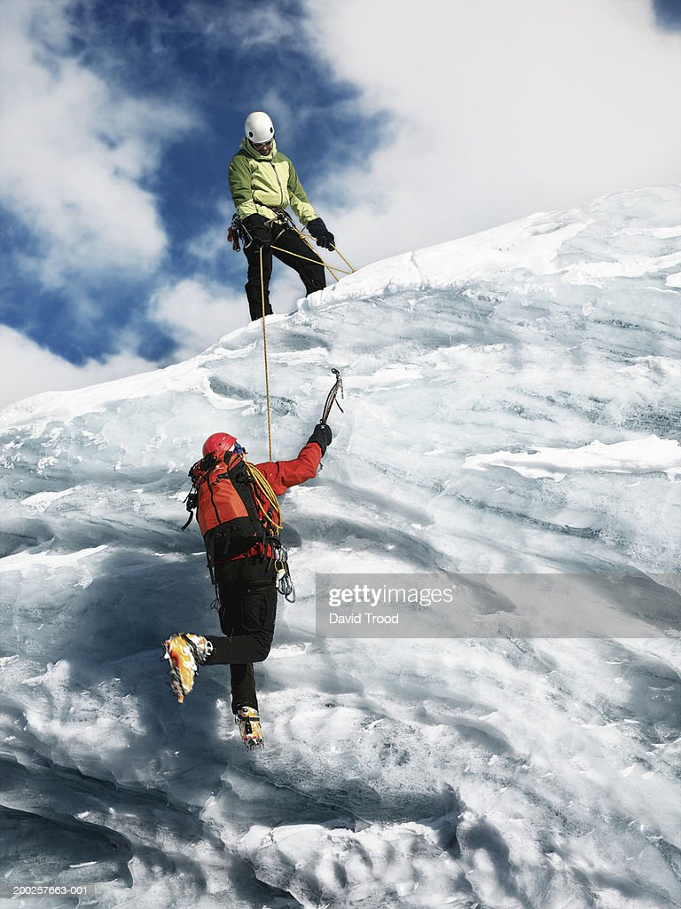 Two male mountain climbers, one holding rope to help other ascend