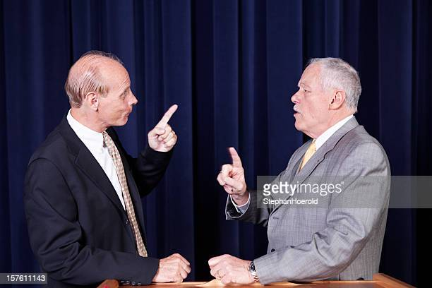 Two male politicians arguing with accusations at a rally