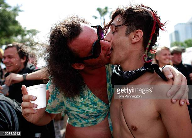 Two male protesters kiss while marching through a downtown street during an organized protest on the first full day of the Republican National...