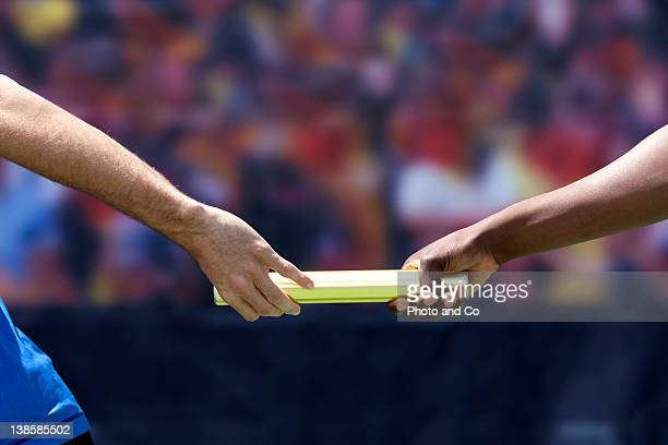 Two male runners passing baton