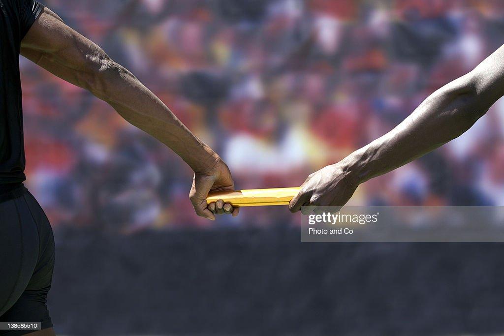 Two male runners passing baton : Stock Photo