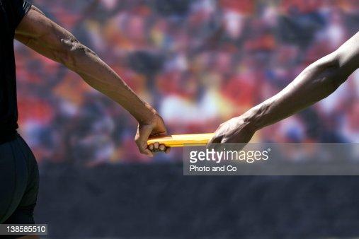 Two male runners passing baton : ストックフォト