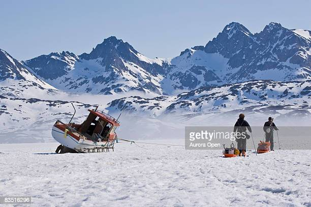 Two male skiers pull sleds carrying supplies as they ski past a fishing boat sitting on ice on a fjord near Tasiilaq, Greenland.