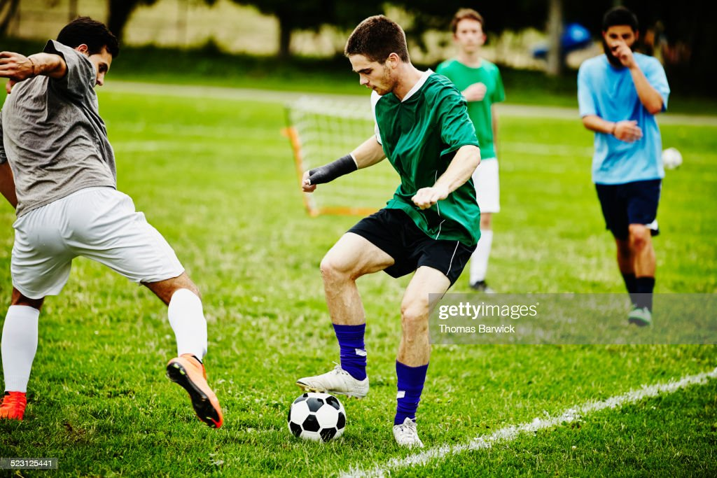 Two male soccer players battling for ball : Stock Photo
