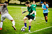 Two male soccer players battling for ball
