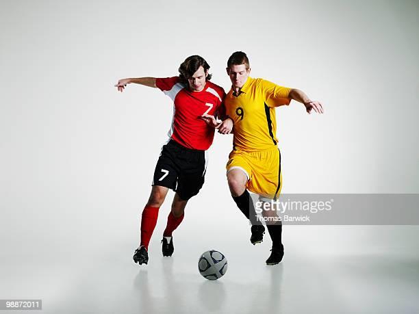 Two male soccer players battling for soccer ball