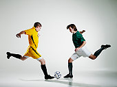Two male soccer players converging on ball