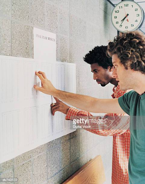 Two Male Students Searching For Their Exam Results on a Notice Board