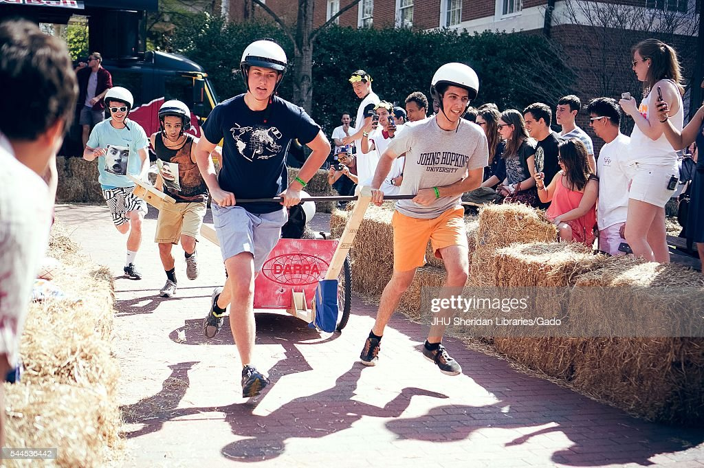 Two male students wearing white helmets pull their teammate in a wooden cart while two students chase from behind onlookers cheering from either side...