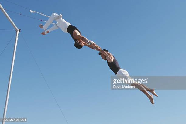 Two male trapeze artists performing, outdoors