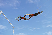 Two male trapeze artists performing release move, outdoors