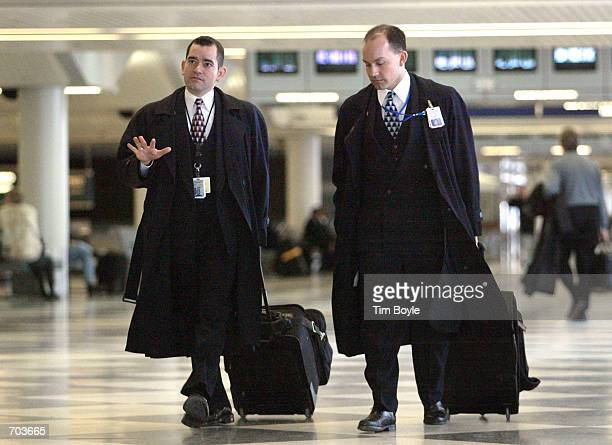 Two male United Airlines flight attendant walks through the airlines terminal February 28 2002 in Chicagos O''Hare International Airport UAL Corps...