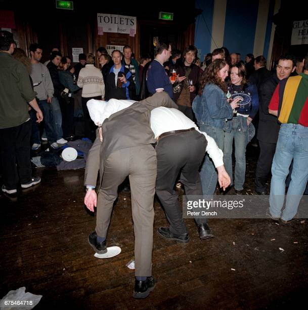 Two male visitors to a beer festival organised by CAMRA in north London make their way towards the toilet March 2001